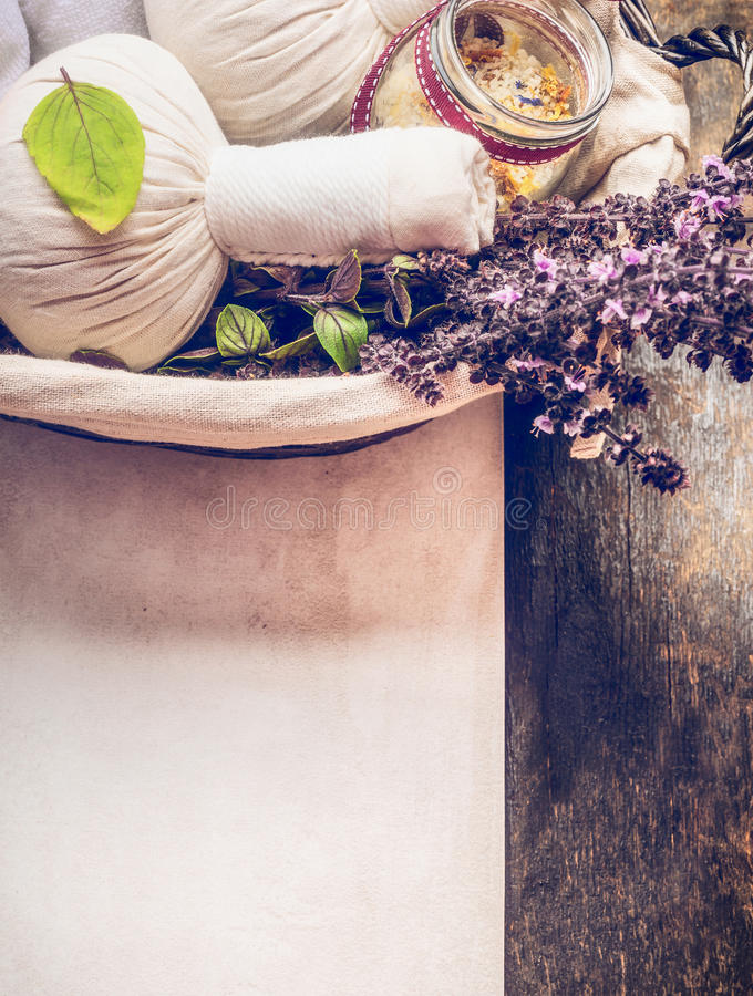 Spa or wellness background with close up of herbal massage compress balls , towel , salt and fresh herbs in basket on wooden backg stock photo