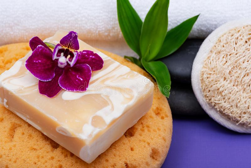 Spa Wellness Concept. Almond Goat milk Soap, Foam Bath&Shower Sea Sponge, Basalt Stones, Natural Loofah Sponge, Bamboo and Orchid. On purple background royalty free stock image