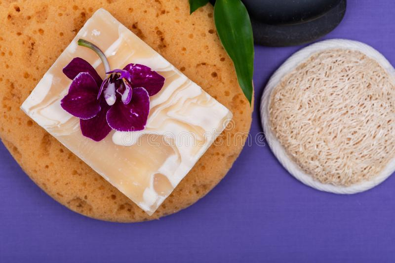 Spa Wellness Concept. Almond Goat milk Soap, Foam Bath&Shower Sea Sponge, Basalt Stones, Natural Loofah Sponge, Bamboo and Orchid. On purple background royalty free stock images