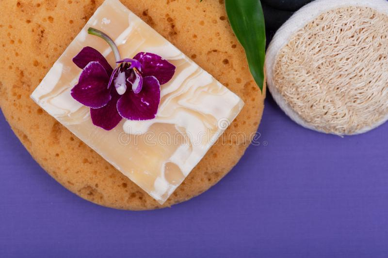 Spa Wellness Concept. Almond Goat milk Soap, Foam Bath&Shower Sea Sponge, Basalt Stones, Natural Loofah Sponge, Bamboo and Orchid. On purple background stock image