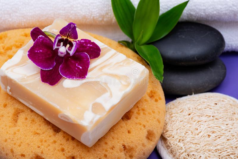 Spa Wellness Concept. Almond Goat milk Soap, Foam Bath&Shower Sea Sponge, Basalt Stones, Natural Loofah Sponge, Bamboo and Orchid. On purple background stock photos