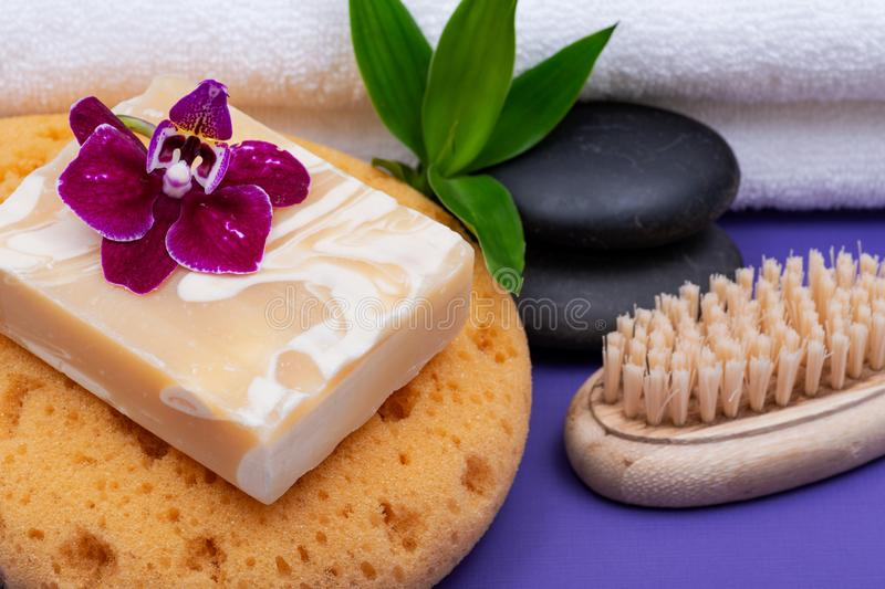 Spa Wellness Concept. Foam Sea Sponge, Almond Goat`s milk Soap, Natural Bristle Wooden Brush, Basalt Stones, Bamboo and Orchid stock images