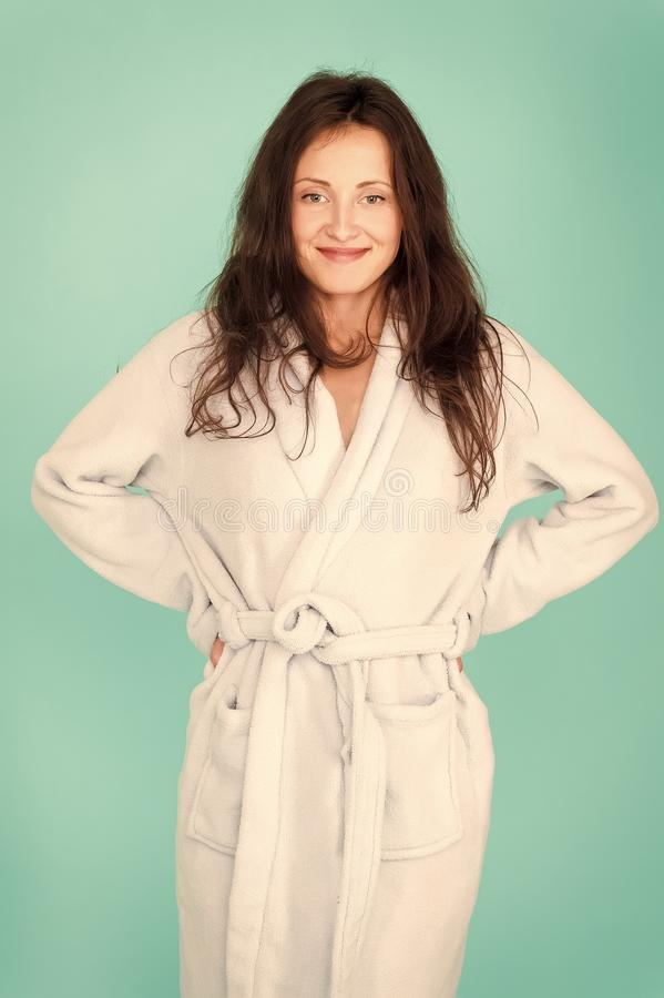 Spa and wellness concept. Girl smiling face long hair wear bathrobe turquoise background. Ready for spa procedures. Woman relaxed after massage session or spa stock photo