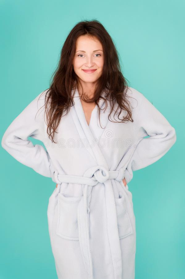 Spa and wellness concept. Girl smiling face long hair wear bathrobe turquoise background. Ready for spa procedures royalty free stock image