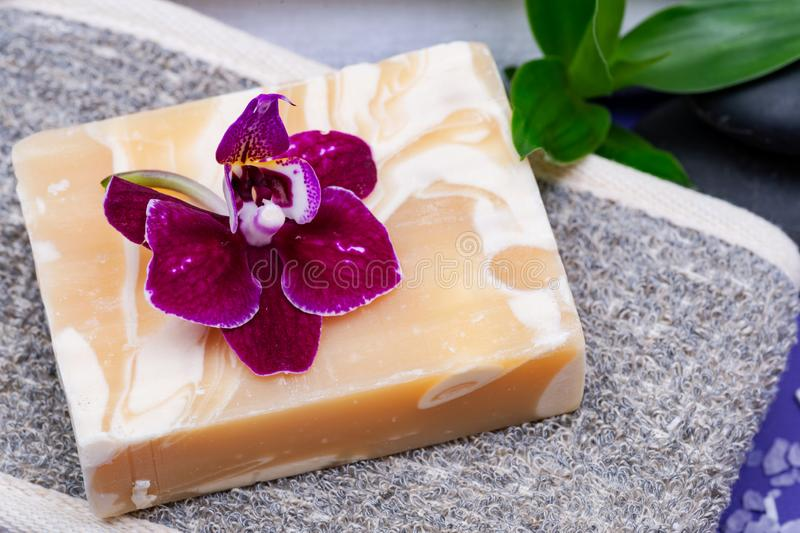 Spa Wellness Concept. Natural Back Scrubber, Almond Goat`s milk Soap, Basalt Stones, Bamboo green leaves and Orchid Flower. On purple background stock photos