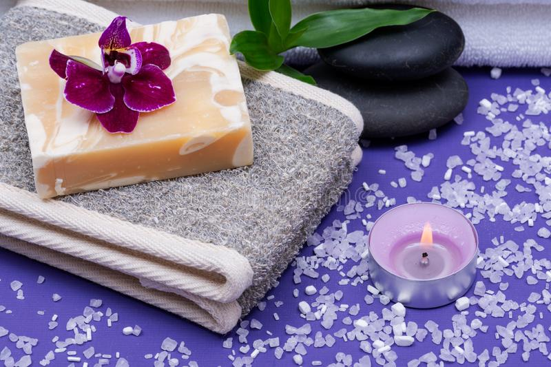 Spa Wellness Concept. Natural Back Scrubber,Goat`s milk Soap, Basalt Stones, Orchid Flower, Bamboo and Lavender Tea Light Candle. On purple background stock photo