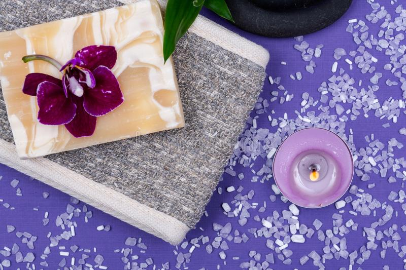 Spa Wellness Concept. Natural Back Scrubber,Goat`s milk Soap, Basalt Stones, Orchid Flower, Bamboo and Lavender Tea Light Candle. On purple background stock image