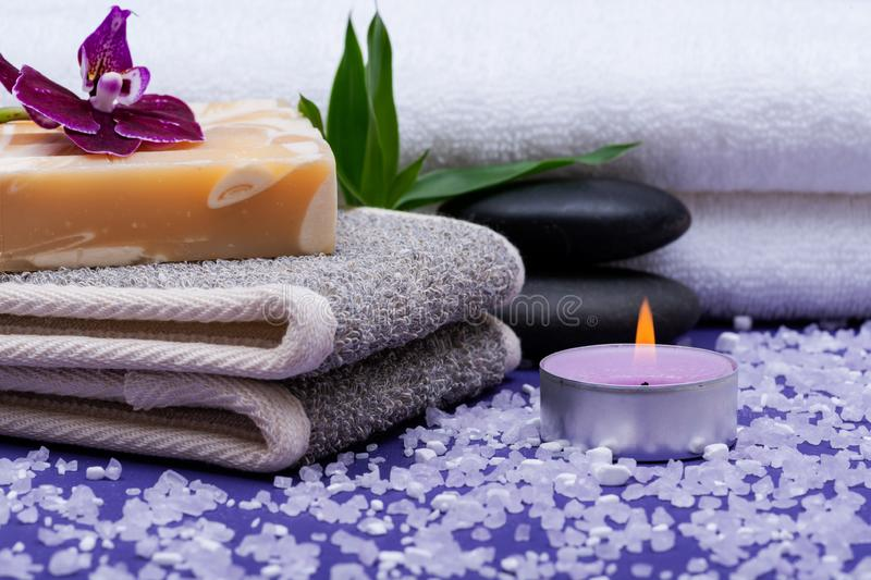 Spa Wellness Concept. Natural Back Scrubber,Goat`s milk Soap, Basalt Stones, Orchid Flower, Bamboo and Lavender Tea Light Candle. On purple background stock photos