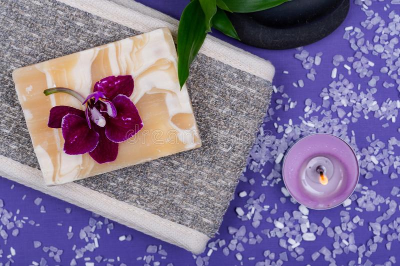Spa Wellness Concept. Natural Back Scrubber,Goat`s milk Soap, Basalt Stones, Orchid Flower, Bamboo and Lavender Tea Light Candle. On purple background royalty free stock images