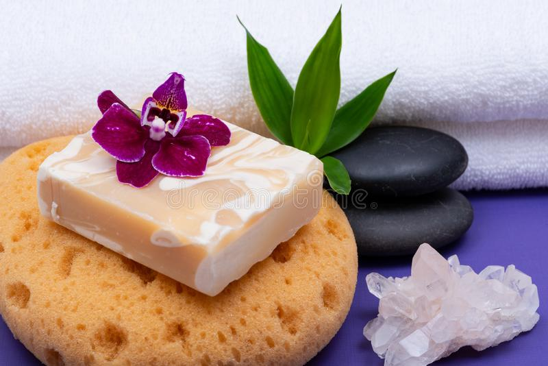 Spa Wellness Concept. Natural Foam Sea Sponge, Goat milk Soap, Basalt Stones, Bamboo, Orchid and Himalayan Clear Quartz Cluster. On purple background stock photo