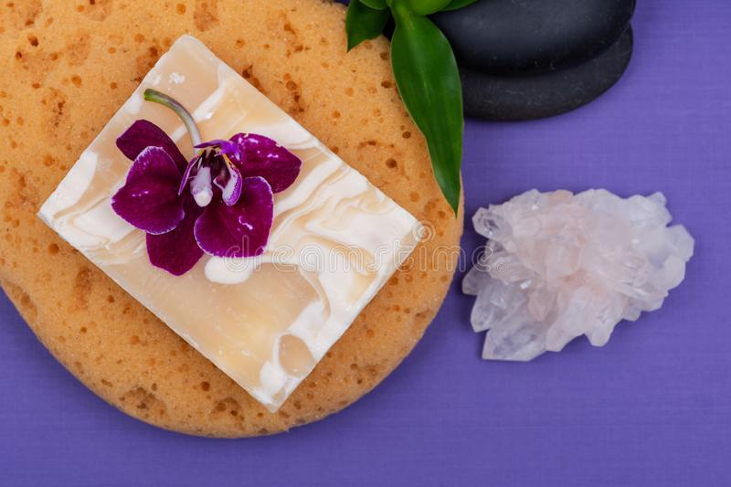 Spa Wellness Concept. Natural Foam Sea Sponge, Goat milk Soap, Basalt Stones, Bamboo, Orchid and Himalayan Clear Quartz Cluster. On purple background royalty free stock image