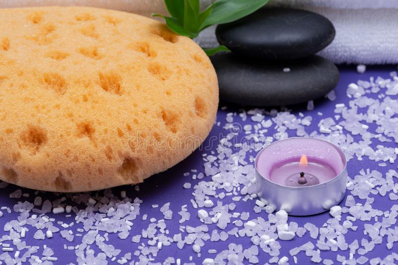 Spa Wellness Concept. Natural Foam Sea Sponge, stacked Basalt Stones, Bamboo, burning Lavender Tea Light Candle and Epsom Salt. On purple background stock image