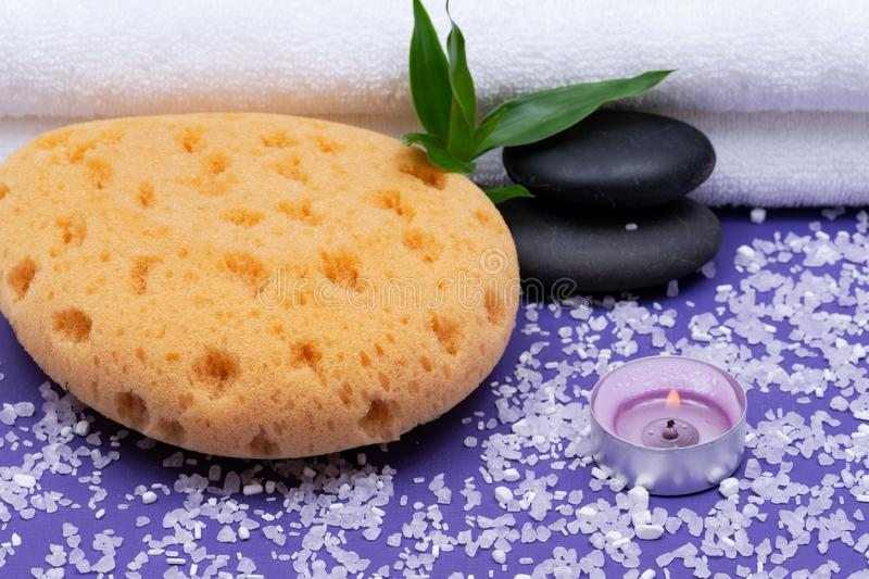 Spa Wellness Concept. Natural Foam Sea Sponge, stacked Basalt Stones, Bamboo, burning Lavender Tea Light Candle and Epsom Salt. On purple background royalty free stock image