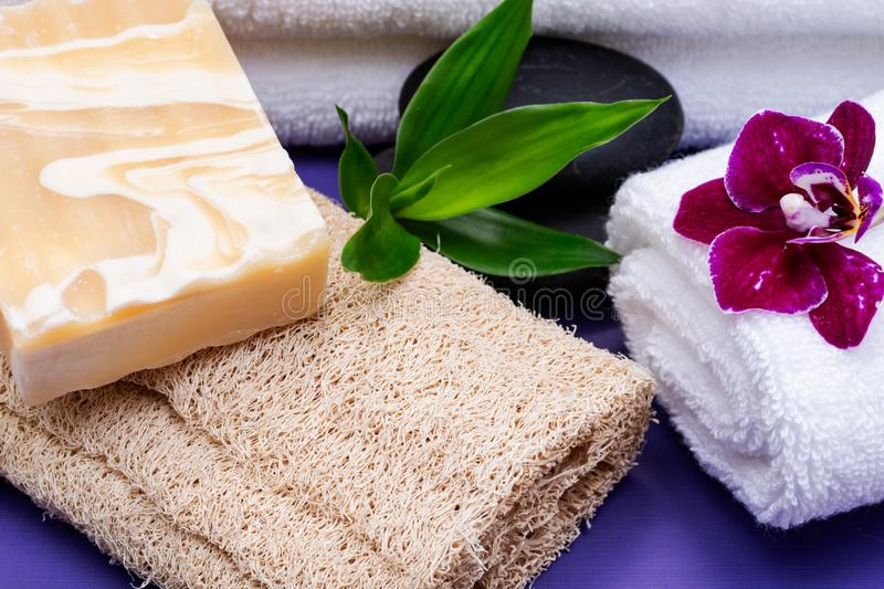 Spa Wellness Concept. Natural Loofah Sponge, Almond Goat& x27;s milk Soap, White Towels, Basalt Stones, Bamboo and Orchid Flower. On purple background royalty free stock photography