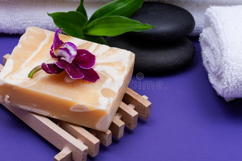 Spa Wellness Concept. Natural Loofah Sponge, Almond Goat`s milk Soap on Wooden Soap Holder, Basalt Stones, Bamboo and Orchid. On purple background stock image