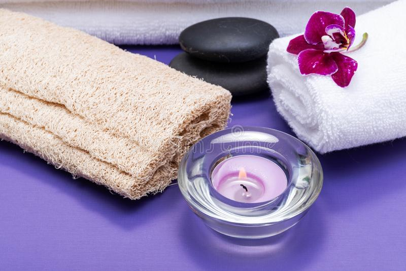 Spa Wellness Concept. Natural Loofah Sponge, rolled up White Towels, Basalt Stones, Orchid and burning Lavender Tea Light Candle. On purple background royalty free stock photos