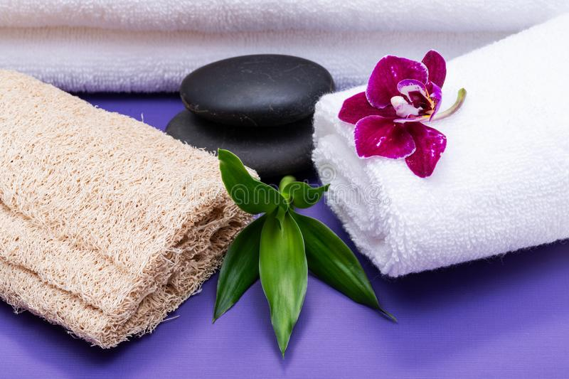 Spa Wellness Concept. Natural Loofah Sponge, rolled up White Towels, stacked Basalt Stones, Bamboo and Orchid Flower on purple royalty free stock photo