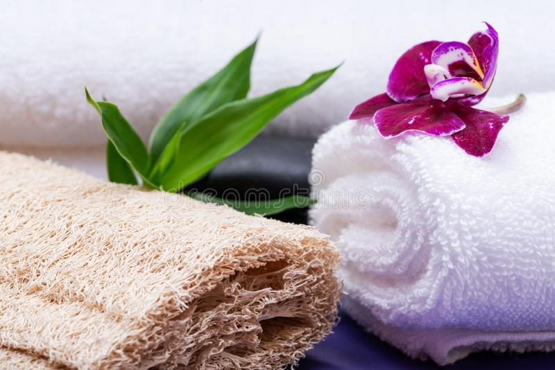 Spa Wellness Concept. Natural Loofah Sponge, rolled up White Towels, stacked Basalt Stones, Bamboo and Orchid Flower on purple. Background stock photos