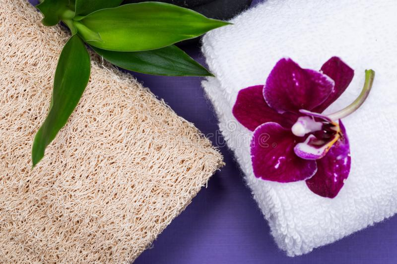 Spa Wellness Concept. Natural Loofah Sponge, rolled up White Towels, stacked Basalt Stones, Bamboo and Orchid Flower on purple. Background stock photo