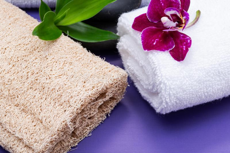Spa Wellness Concept. Natural Loofah Sponge, rolled up White Towels, stacked Basalt Stones, Bamboo and Orchid Flower on purple. Background stock images