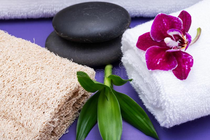 Spa Wellness Concept. Natural Loofah Sponge, rolled up White Towels, stacked Basalt Stones, Bamboo and Orchid Flower on purple. Background royalty free stock photography