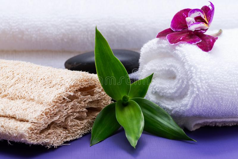 Spa Wellness Concept. Natural Loofah Sponge, rolled up White Towels, stacked Basalt Stones, Bamboo and Orchid Flower on purple. Background stock photography