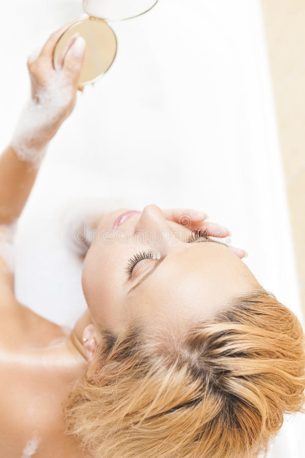 Spa and Wellness Concepts and Ideas. Caucasian Blond Woman During Skin Makeup. Process in Bathtub. Vertical Image stock images