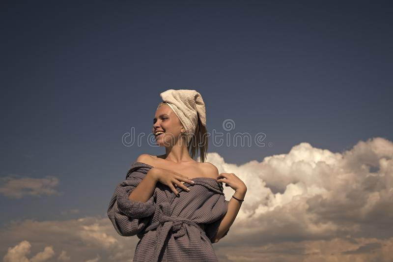 Spa and wellness. Girl smiling on cloudy blue sky. Happy model enjoying sunny day. Summer vacation concept. Woman in bathrobe and towel on head royalty free stock images