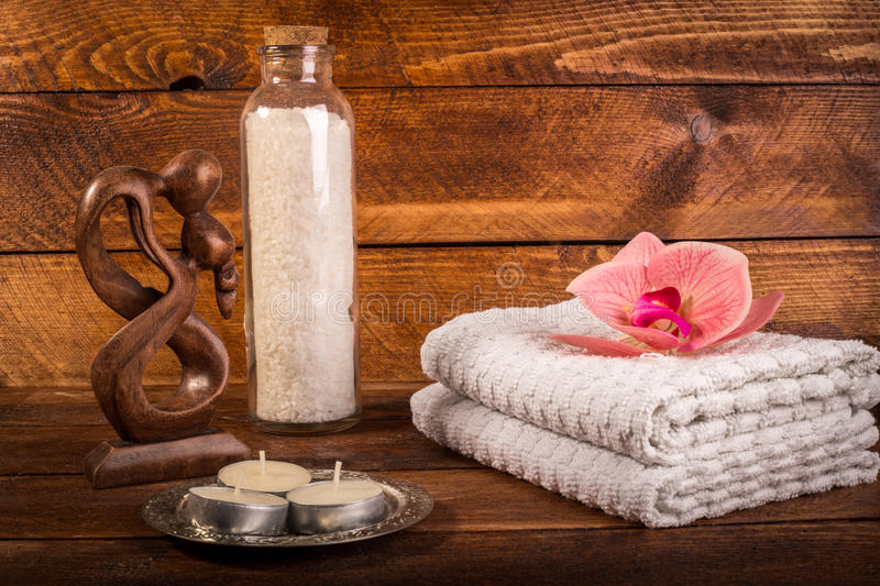 Spa or wellness set. White sea salt in white glass bottle, candle, towels, brown wooden statuette and pink flowers lily on brown stock images