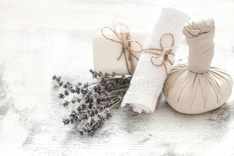 Spa and wellness setting with flowers and towels. Bright composition with lavender flowers. Dayspa nature products with coconut. Spa and wellness setting with stock photography
