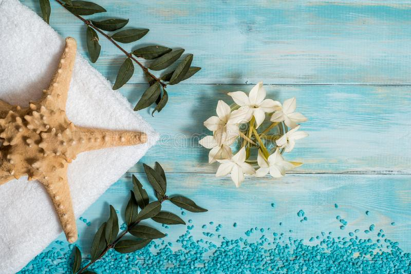 Spa and wellness setting with flowers, and white towel on old wooden background. Blue dayspa nature set. copyspace. Vacation. Concept. flat lay. top view royalty free stock image