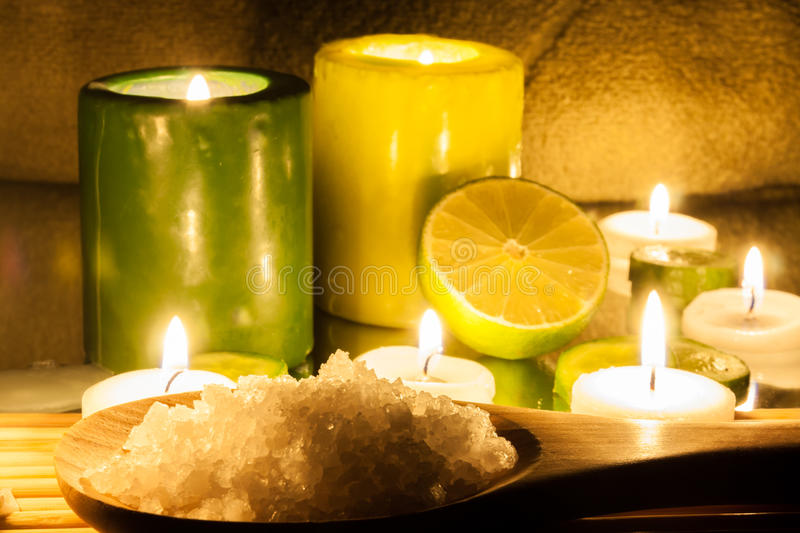 Spa and wellness setting green and yellow candles lit, lemon Green. Bathing salt royalty free stock photography