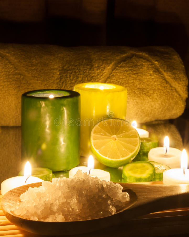 Spa and wellness setting green and yellow candles lit, lemon Green. Bathing salt royalty free stock photo