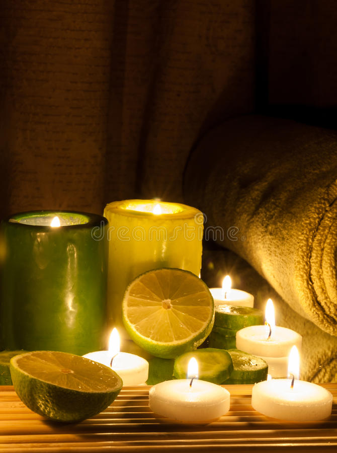 Spa and wellness setting green and yellow candles lit, lemon Green. Spa Concept green and yellow candles lit, lemon Green royalty free stock images