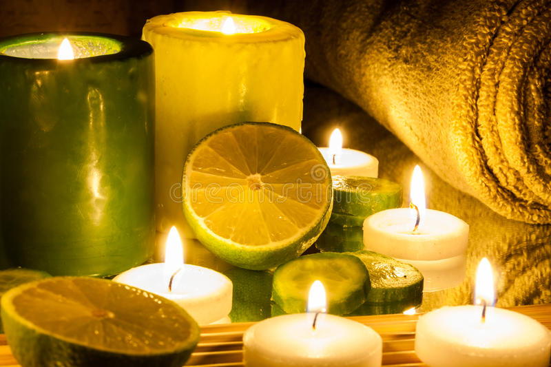Spa and wellness setting green and yellow candles lit, lemon Green. Spa Concept green and yellow candles lit, lemon Green royalty free stock image