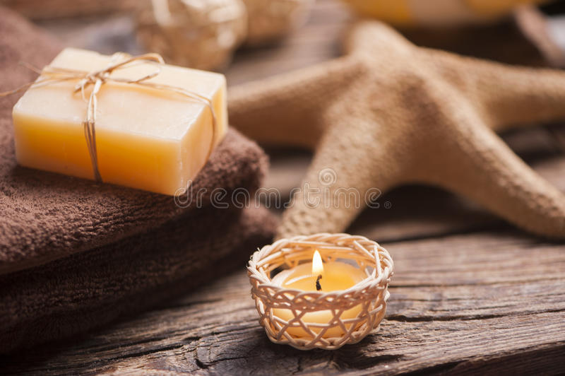 Spa and wellness setting with natural soap, candles and towel royalty free stock image