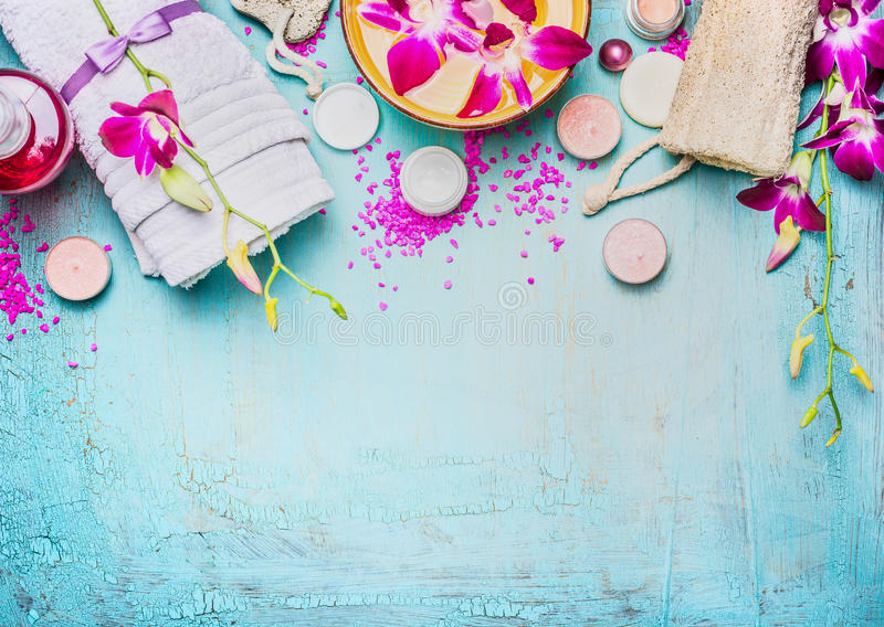 Spa or wellness setting with pink purple orchid flowers , bowl of water, towel, cream , sea salt and nature sponge on turquoise bl. Ue background, top view royalty free stock photography