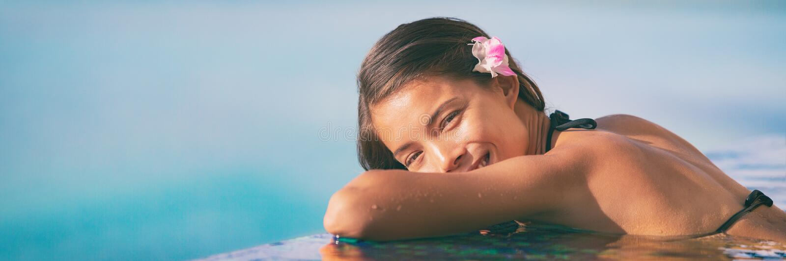 Spa wellness woman relaxing in blue panoramic banner. Happy Asian woman at luxury hotel resort  infinity pool royalty free stock photo
