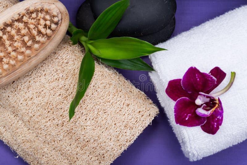 Spa wellnessbegrepp Naturlig luffasvampsvamp, träborste för naturligt borst, vita handdukar, basaltstenar, bambu och orkidéblomma arkivfoto