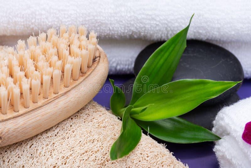 Spa wellnessbegrepp Naturlig luffasvampsvamp, träborste för naturligt borst, vita handdukar, basaltstenar, bambu och orkidéblomma royaltyfria bilder