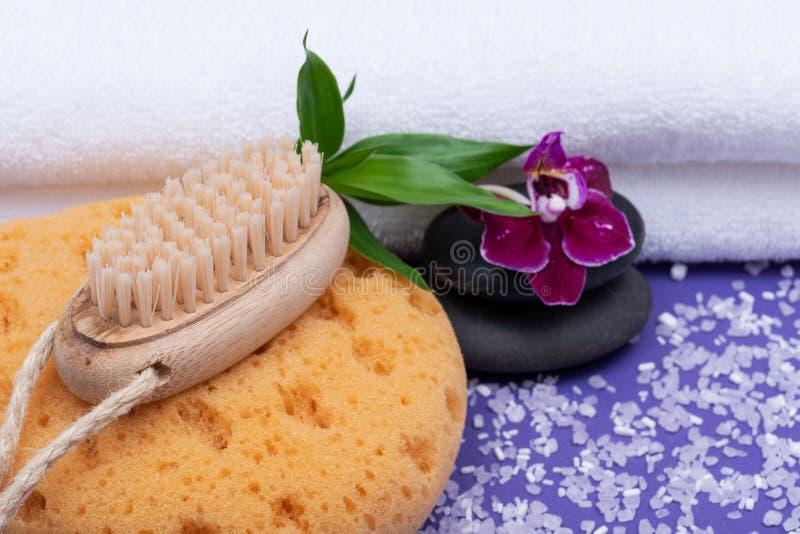 Spa wellnessbegrepp Skumma bad- & duschhavssvampen, den träborsten för naturligt borst, basaltstenar, bambu och orkidéblomman royaltyfri foto