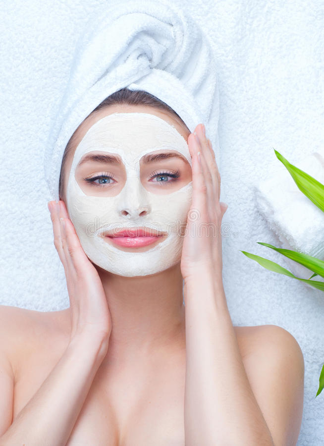 Spa woman applying facial clay mask. Closeup portrait of beautiful girl with a towel on her head applying facial mask royalty free stock photo