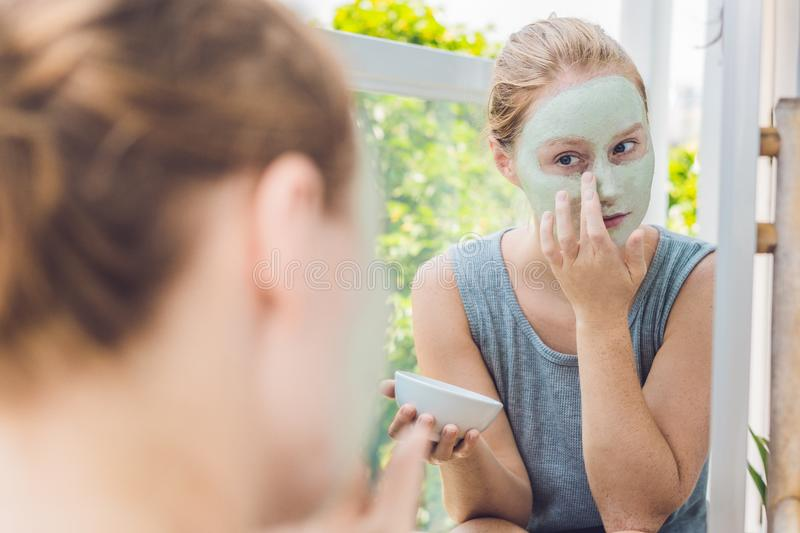 Spa Woman applying Facial green clay Mask. Beauty Treatments. Cl royalty free stock photo