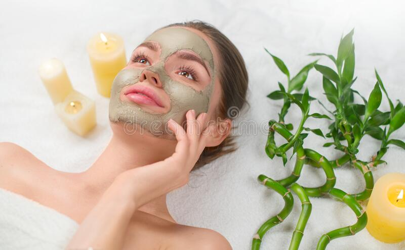 Spa Woman applying Facial green clay Mask. Beauty Treatments. Close-up portrait of beautiful girl in spa salon. Dayspa. Spa Woman applying Facial green clay Mask stock photo