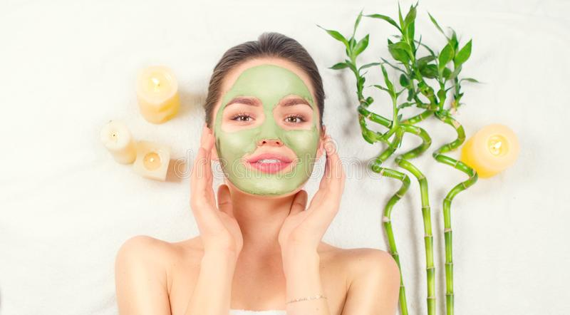 Spa Woman applying Facial green clay Mask. Beauty Treatments. Close-up portrait of beautiful girl in spa salon royalty free stock photo