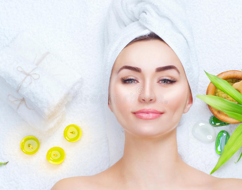 Spa woman applying facial mask. Closeup portrait of beautiful girl with a towel on her head applying facial clay mask royalty free stock photography