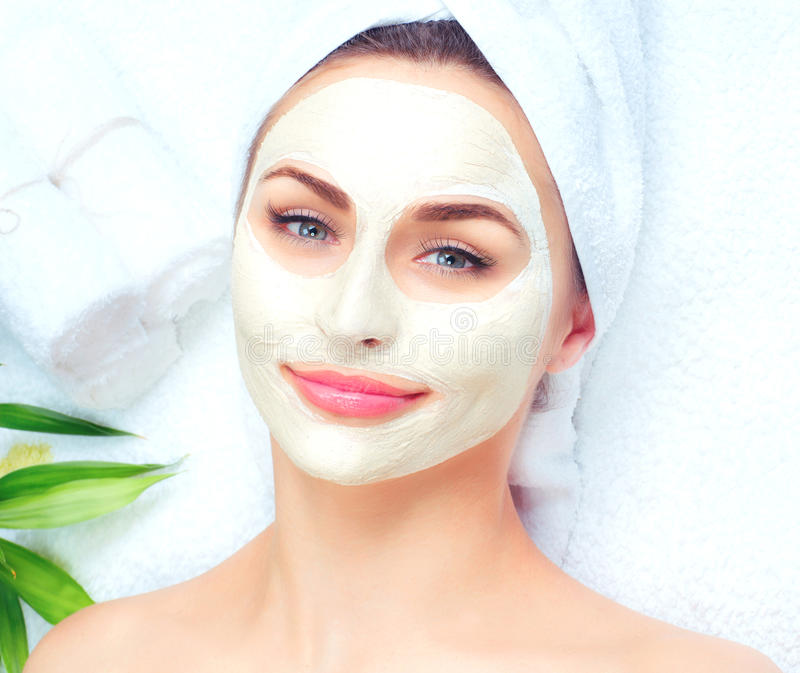 Spa woman applying facial mask. Closeup portrait of beautiful girl with a towel on her head applying facial clay mask royalty free stock photo