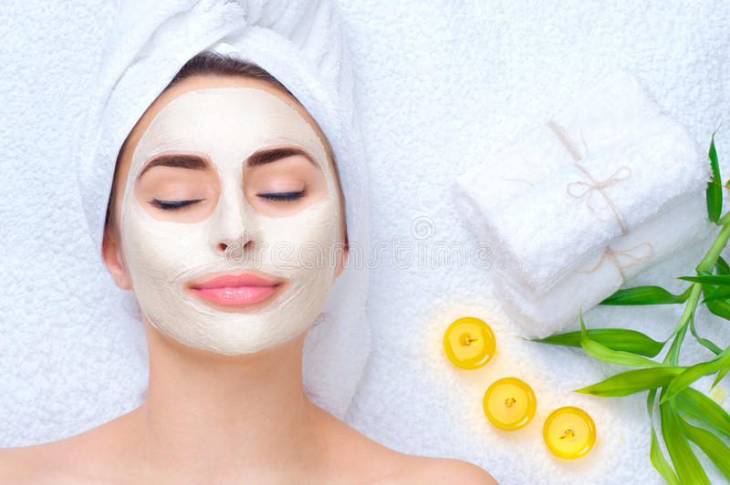 Spa woman applying facial mask. Closeup portrait of beautiful girl with a towel on her head applying facial clay mask stock photos