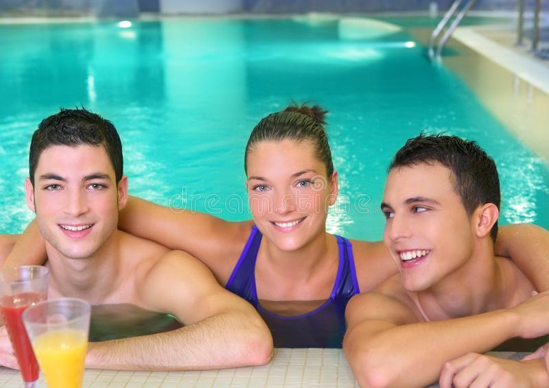 Spa young friends group smiling on turquoise pool royalty free stock photo