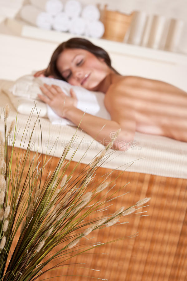 Spa - Young woman at wellness therapy massage. Treatment, focus on grass in foreground stock image